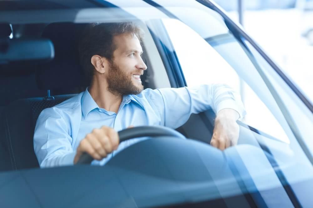 Zadowolony mężczyzna w nowym zarejestrowanym samochodzie